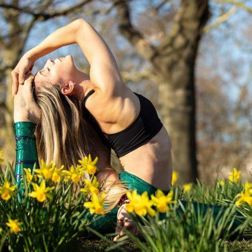 Ambra Vallo practicing yoga amongst daffodils
